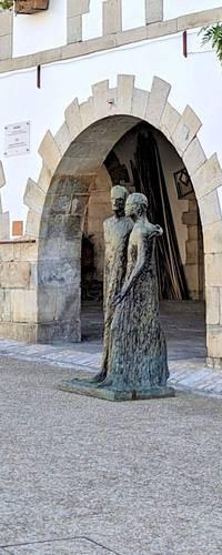 Sculpture de couple devant arcades à La Bastide-Clairence